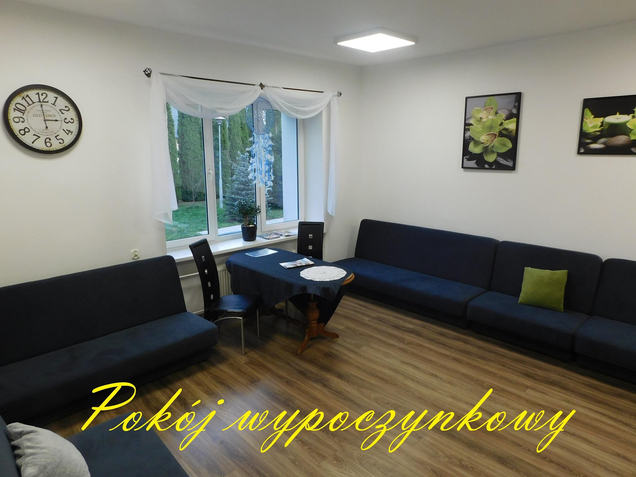 na zdjęciu widoczne wnętrze pokoju wypoczynkowego, przy ścianach sofy, pod oknem stolik z dwoma krzesłami, jednej ścianie widoczny duży ozdobny zegar, na drugiej ścianie wiszą dwa obrazy z motywem roślinnym.