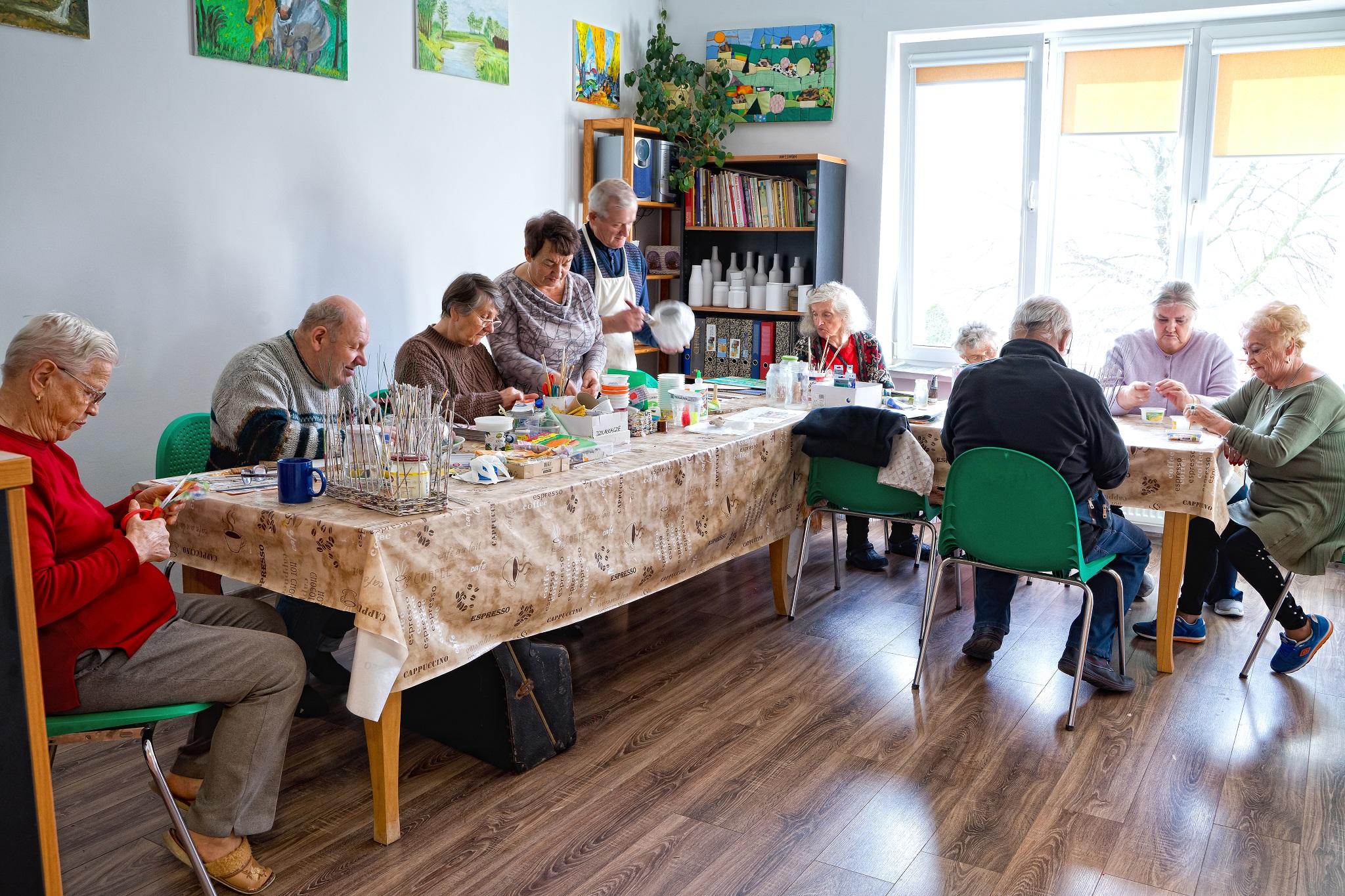Na zdjęciu widać seniorów przy stole w kształcie litery L wykonujących ozdoby.