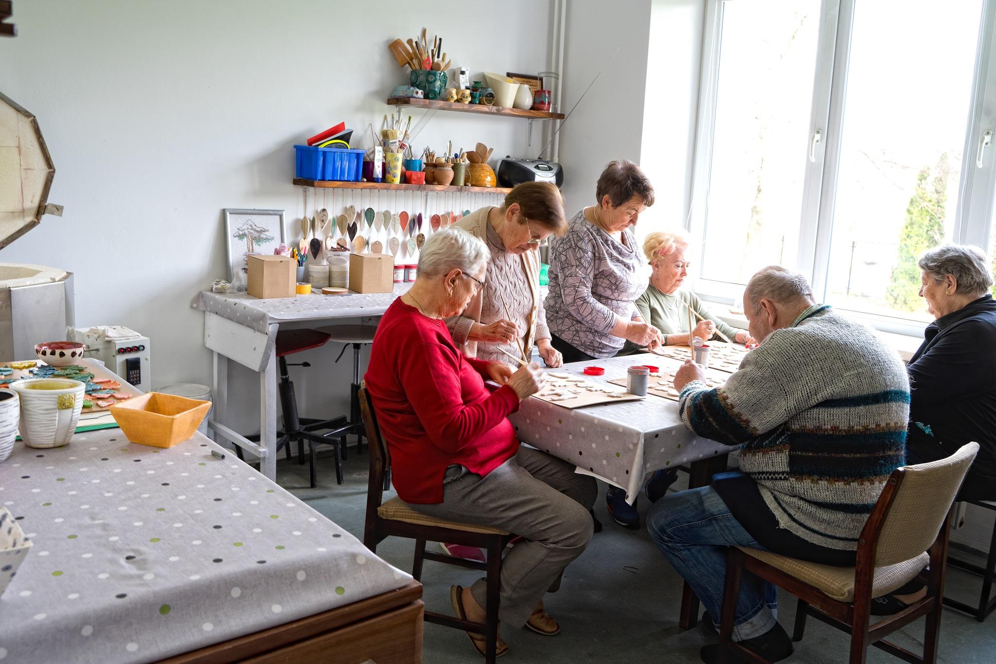 Na zdjęciu przedstawione wnętrze pracowni ceramicznej, seniorzy siedzący przy stole wykonujący ozdoby ceramiczne.