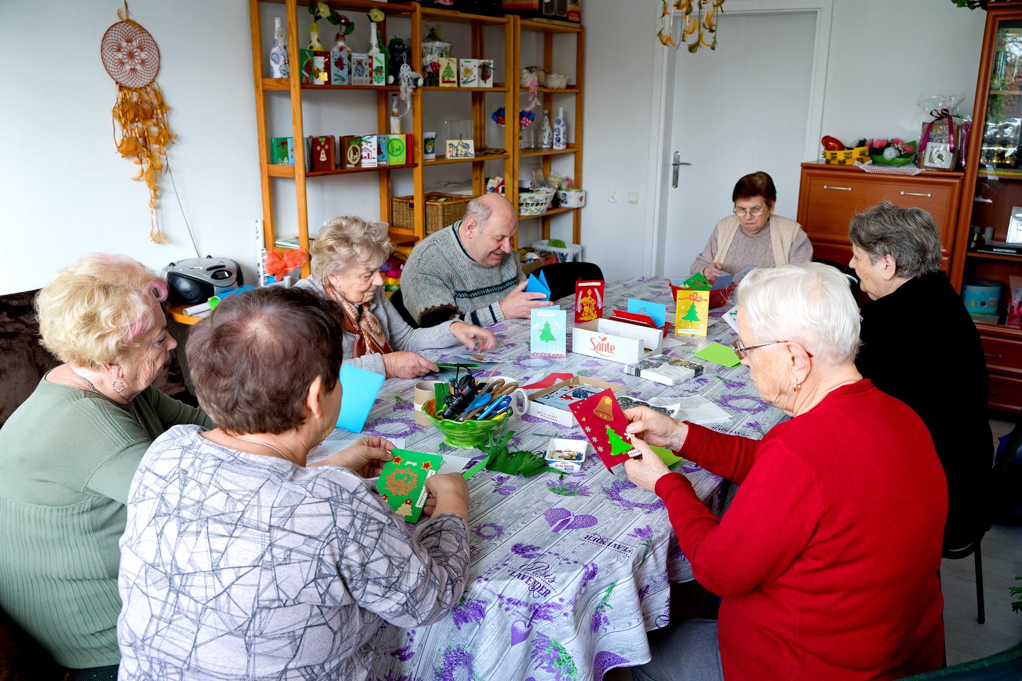 Na zdjęciu seniorzy siedzący przy stole i wykonujący kartki świąteczne.