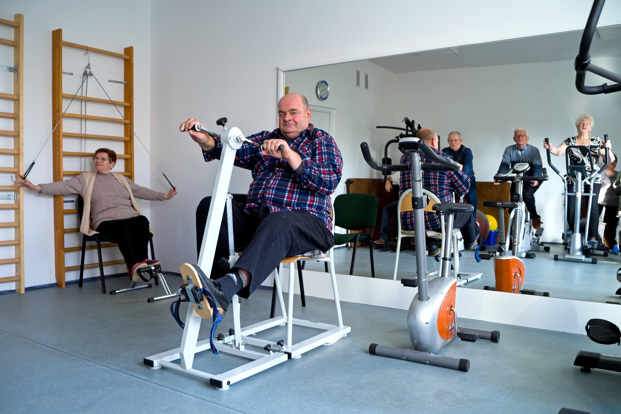 Sala zajęć ruchowych, na pierwszym planie mężczyzna ćwiczący na rowerze rehabilitacyjnym, w tle kobieta siedząca przy drabinkach w trakcie ćwiczeń rehabilitacyjnych, w lustrze na ścianie widać inne osoby ćwiczące na rowerach rehabilitacyjnych