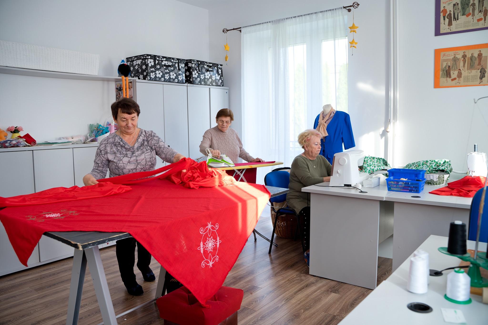 Na zdjęciu przedstawione wnętrze pracowni krawieckiej, na pierwszym planie kobieta rozkładająca materiał na stole krojczym, na drugim planie kobieta siedząca przy biurku obsługująca maszynę do szycia, w tle kobieta prasująca fragment materiału.